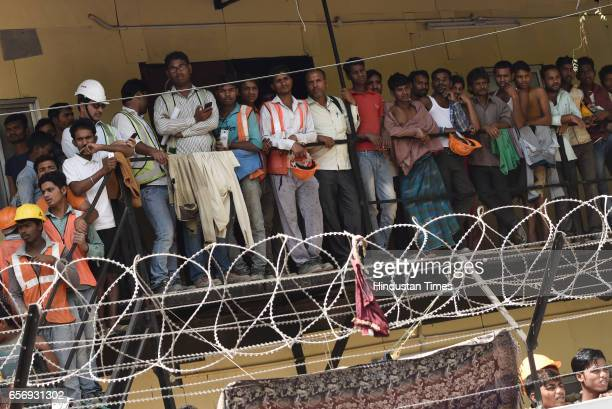 Construction labourers watch a demonstration by lawyers who were protesting to oppose the Bar Council of India's suggestion to the Law Commission to...