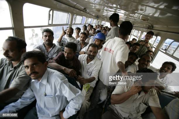 Construction Labourers working in the Dubai Marina area board a bus which will take them back to their labour camp for the night on May 1 2006 in...