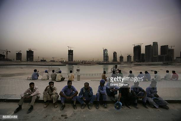 Construction Labourers working in the Dubai Marina area wait to board a bus which will take them back to their labour camp for the night on May 1...