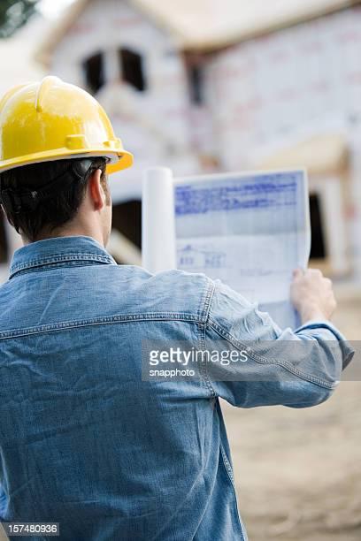 Construction homme tenant plan portant Chapeau dur