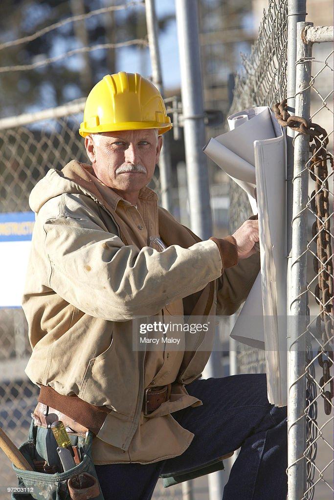 Construction man  holding blueprints wit tool belt : Stock Photo