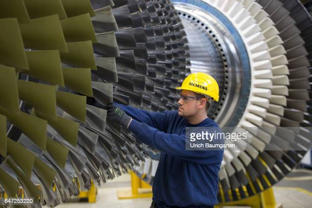 Construction of gas turbines at Siemens AG in Berlin Technician during control work on a gas turbine