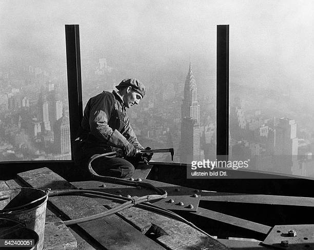 Construction of skyscrapers in Manhattan A worker welding steel girders during the construction of a skyscraper in Manhattan in the background is the...