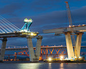 Construction ongoing at night on the new bridge crossing the Firth of Forth, between Fife and the Lothians.