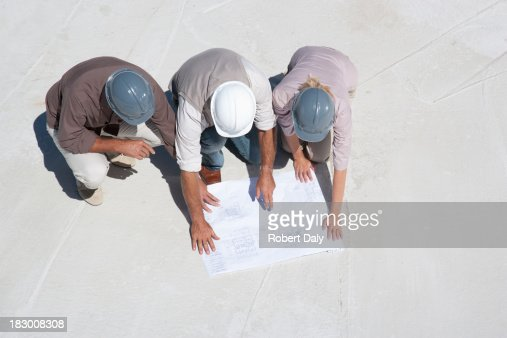 Construction people viewing blueprints at construction site : Stock Photo