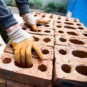 Bricklayer with brick at a construction site.