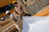 Construction plan with carpenters framing a house