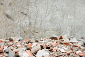 Construction rubble, broken bricks, pieces of concrete against wall