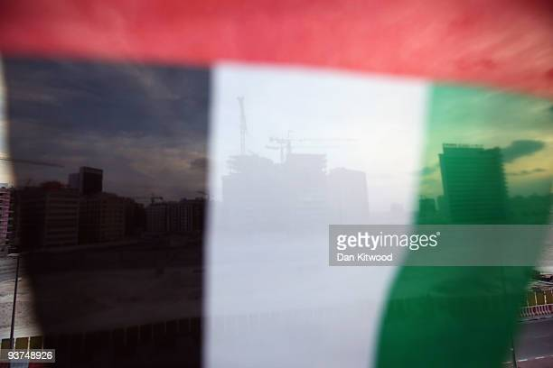 A construction site is seen behind an UAE flag on December 3 2009 in Dubai United Arab Emirates Stock markets in the Dubai and Abu Dhabi fell sharply...