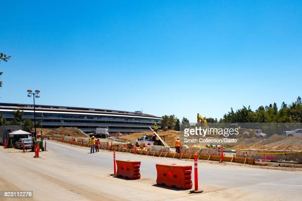Construction site with construction workers and equipment as well as a portion of the main building at the Wolfe Street entrance of the Apple Park...