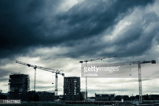 Construction Site with Cranes and Cloudy Sky