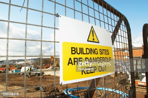 Construction site with danger sign hanging on the access gate.