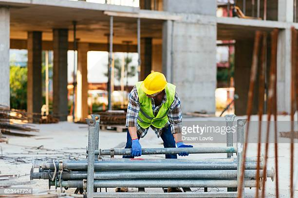 Construction site worker lifting steel bars on construction platform