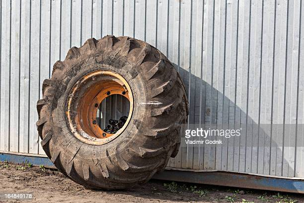 Construction vehicle wheel leaning against industrial building