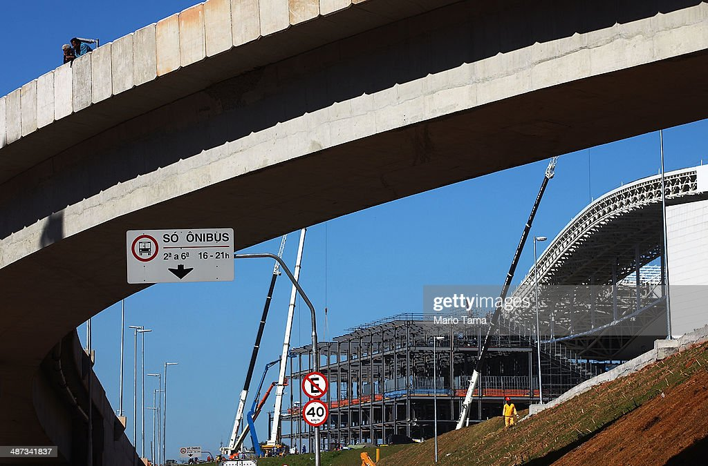 Construction work continues on an access road (TOP) at the Itaquerao stadium, also known as Arena de Sao Paulo and Arena Corinthians, on April 29, 2014 in Sao Paulo, Brazil. The stadium is scheduled to host the opening World Cup match on June 12 between Brazil and Croatia. Some 20,000 temporary seats are being constructed behind the goals to boost the seating capacity to nearly 70,000.