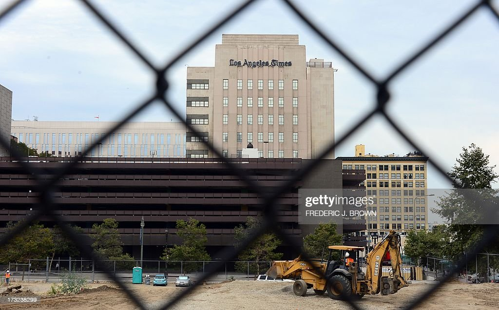 Construction work takes place near the Los Angeles Times Building in downtown Los Angeles, California on July 10, 2013. The Tribune Company, a group which owns 23 television stations, announced plans Wednesday to spin off its newspaper division, which includes the Los Angeles Times and Chicago Tribune, separating the struggling unit from its growing television station holdings. Tribune Company last week announced a $2.7 billion deal to buy 19 more local television stations and has said splitting into two distinct companies would give each 'greater financial and operational focus.' AFP PHOTO/Frederic J. BROWN