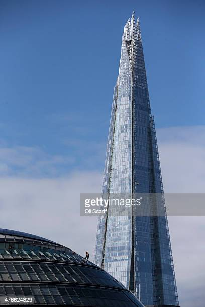 A construction worker abseils down the outside of City Hall in front of The Shard skyscraper on March 4 2014 in London England