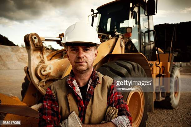 construction worker against earth mover in background