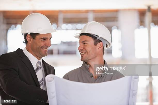 Trabajador de construcción y empresario mirando a blueprints en solar de construcción