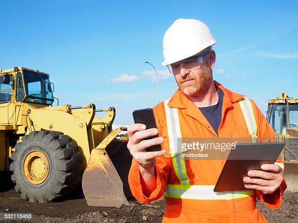 Bauarbeiter und Computer und Handy-Technologie