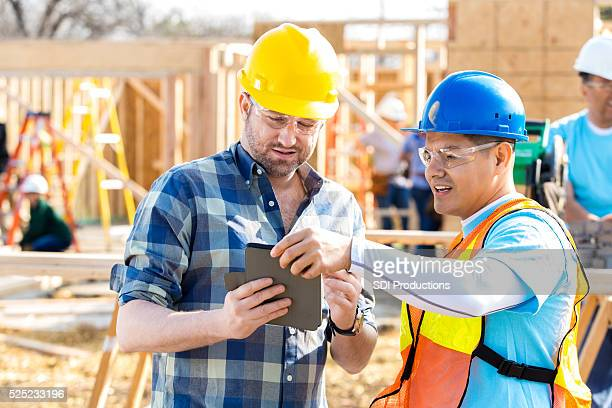Construction worker and foreman review building plans