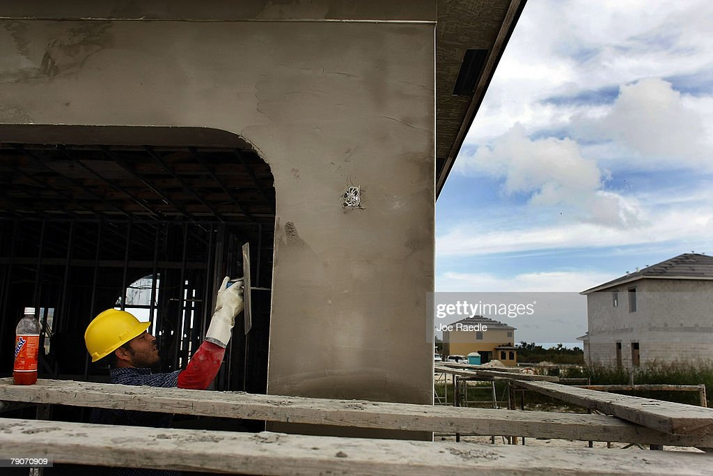 A construction worker applies cement to a home under construction January 17, 2008 in Miami, Florida. The Commerce Department released figures showing that new home construction is down 24.8 percent from 2006.