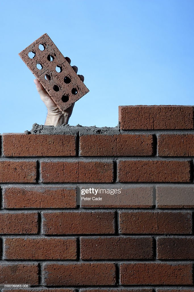 Construction worker behind wall, holding brick : Stock Photo