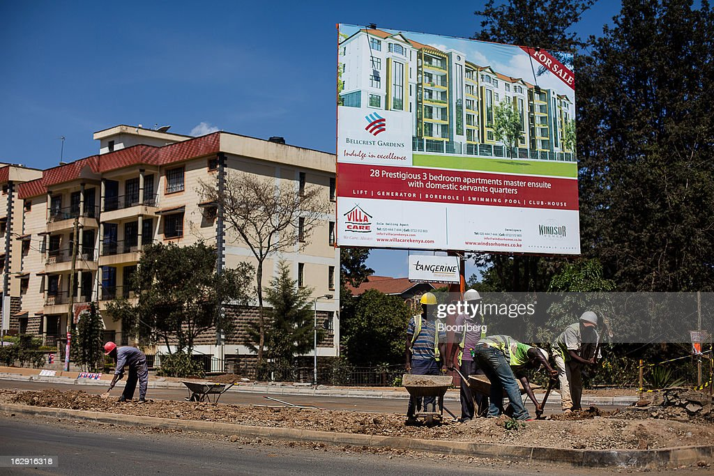 Construction worker build a new road past an advertisement for a new development of residential apartments in Nairobi, Kenya, on Friday, March 1, 2013. Next week's presidential vote will be the first since disputed elections in 2007 triggered ethnic fighting in which more than 1,100 people died and another 350,000 fled their homes. Photographer: Trevor Snapp/Bloomberg via Getty Images