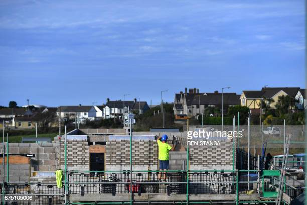 A construction worker builds a wall at Nansledan housing development championed by Britain's Prince Charles Prince of Wales at Newquay town in...