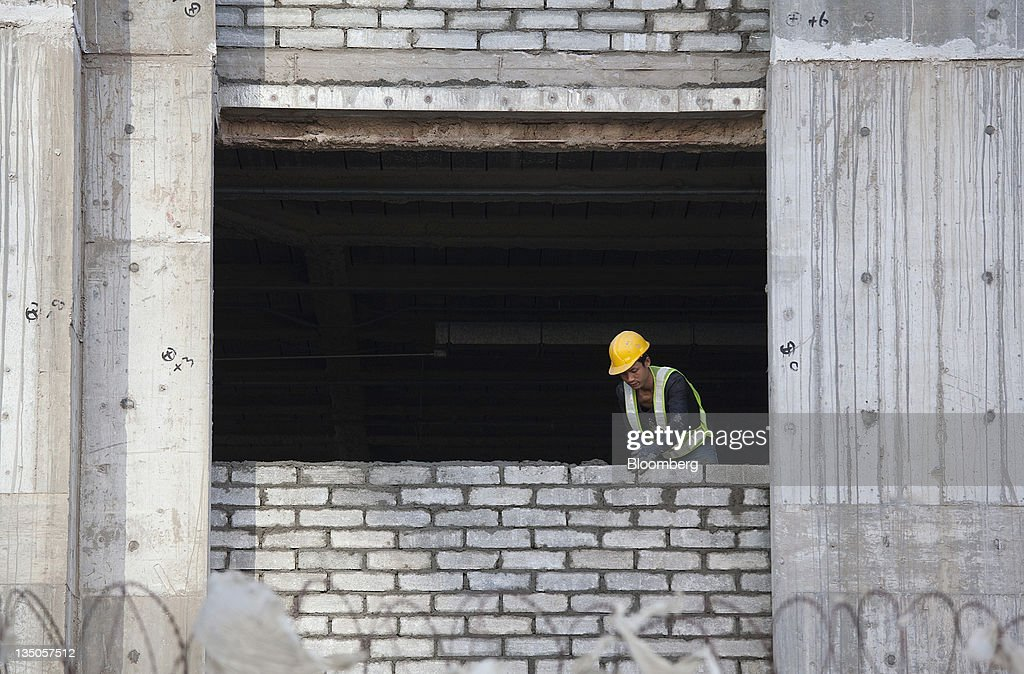 A construction worker builds a wall at the Conrad Macao hotel site on the Cotai Strip in Macau, China, on Sunday, Dec. 4, 2011. Macau casino gambling revenue climbed a better-than-expected 33 percent last month as economic growth stoked demand from visitors from China's mainland. Photographer: Jerome Favre/Bloomberg via Getty Images