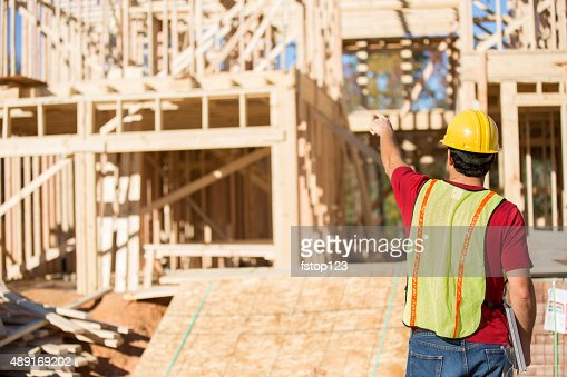 Construction worker busy working at job site. Framed building. Materials.