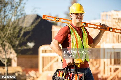 Construction worker busy working at job site. Framed building. Tools.