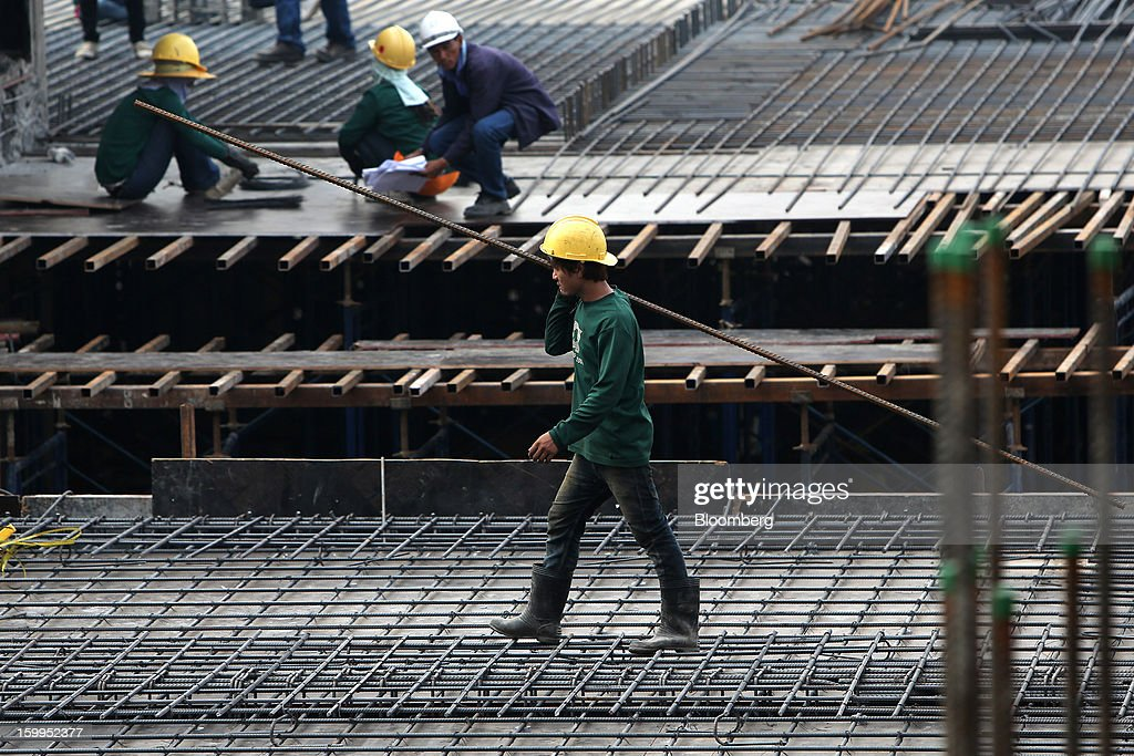 A construction worker carries materials on a building site at Siam Square in Bangkok, Thailand, on Wednesday, Jan. 23, 2013. Prime Minister Yingluck Shinawatra's government last month approved a new round of increases in the daily minimum wage to 300 baht ($9.8) from the beginning of this year, after a similar raise in April in seven provinces including Bangkok. Photographer: Dario Pignatelli/Bloomberg via Getty Images
