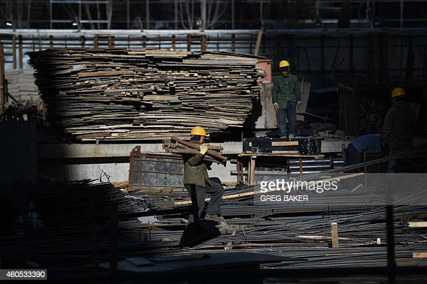 A construction worker carries steel pipes on a building site in Beijing on December 16 2014 Foreign investment into China accelerated in November...