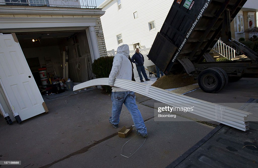 A construction worker carries supplies while doing repairs on a home in the Staten Island borough of New York, U.S., on Wednesday, Nov. 28, 2012. Superstorm Sandy is giving the U.S. Northeast, and the rest of the country, an economic boost that may eventually surpass the loss of business it caused. Photographer: Jin Lee/Bloomberg via Getty Images