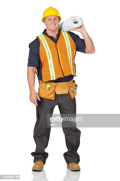 Construction worker carrying blueprints