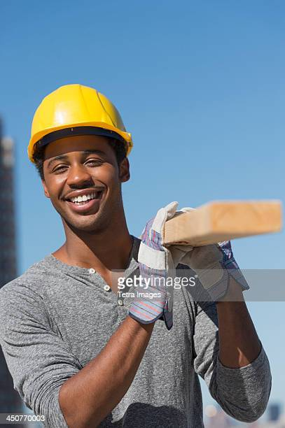 Construction worker carrying plank