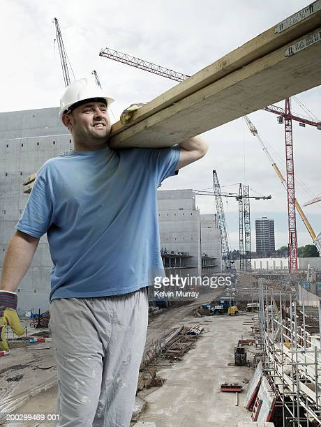 Construction worker carrying planks on building site, smiling