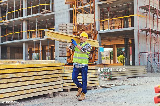 Construction worker carrying planks