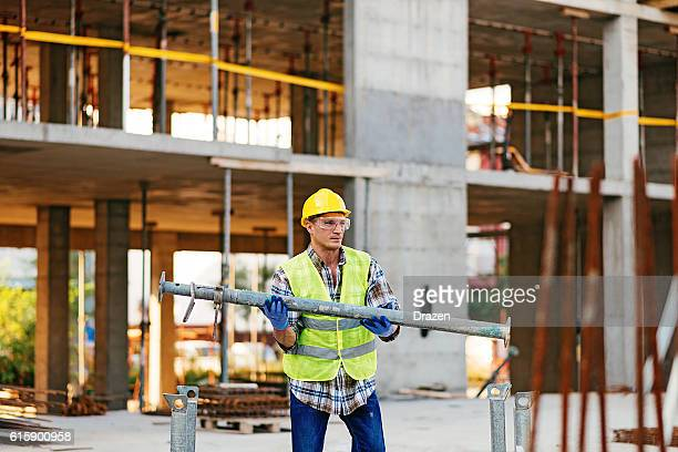 Construction worker carrying steel rod