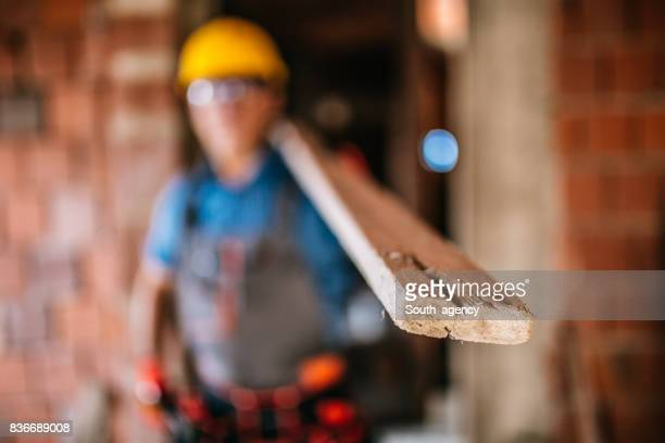 Construction worker carrying wood plank