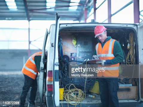 Construction worker checking clipboard in back of van on building site
