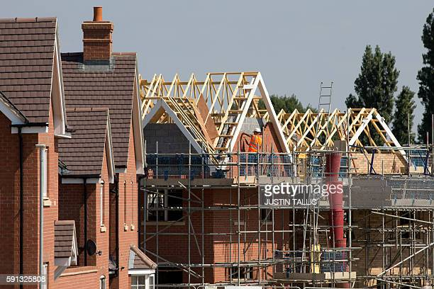 A construction worker completes the brick work on the apex of a house on a housing estate in New Cardington near Bedford north of London on August 17...