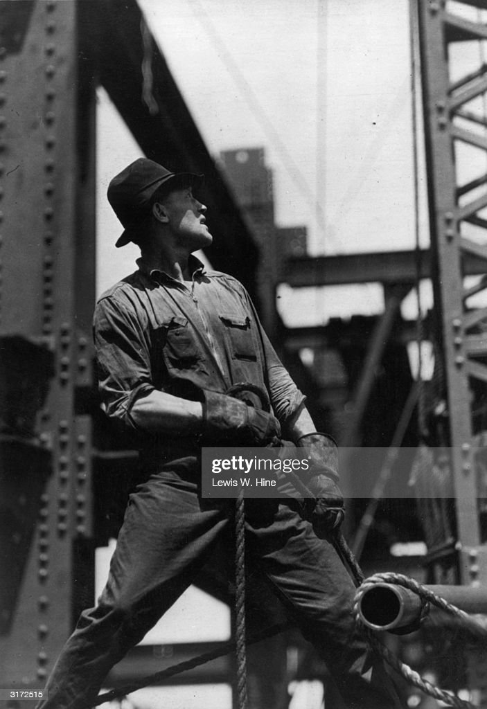 A construction worker concentrates on lifting an object with a pulley while working on the Empire State Building, New York City. He wears coveralls, a hat and gloves.