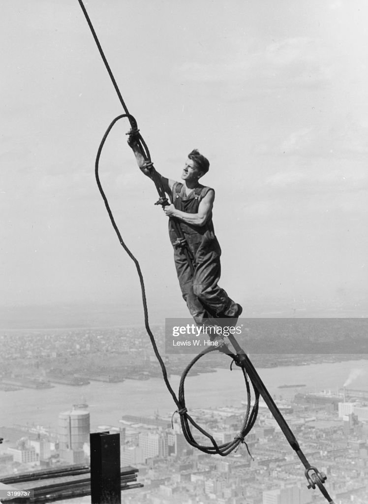 A construction worker connects two cables suspended high above the New York during the construction of the Empire State Building.