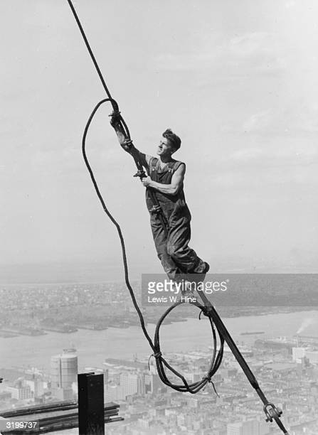 A construction worker connects two cables suspended high above the New York during the construction of the Empire State Building