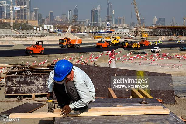 A construction worker cuts a 2x4 with an electric saw The modern skyline of Dubai road construction and cranes are seen in the background The...