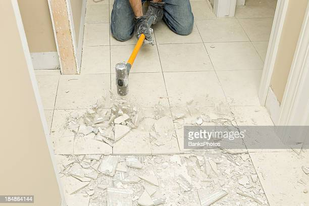 Construction Worker Demolishing Hallway Tile with Sledgehammer