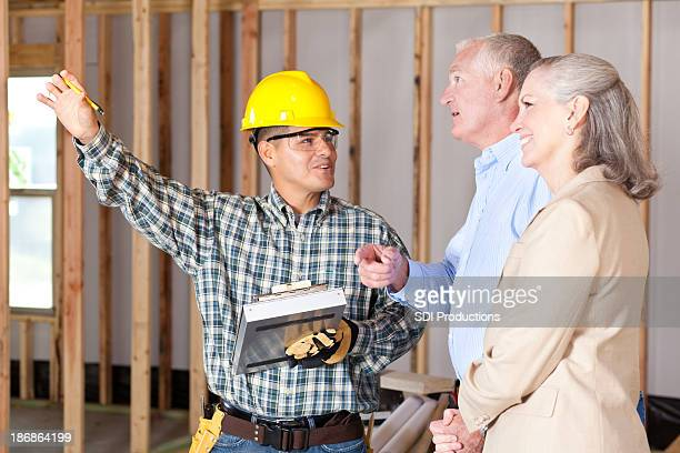 Construction worker discussing house building with home owners