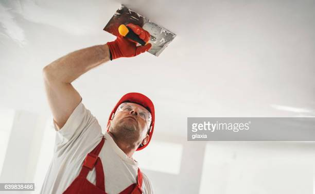 Construction worker doing a hard a finish of a ceiling.